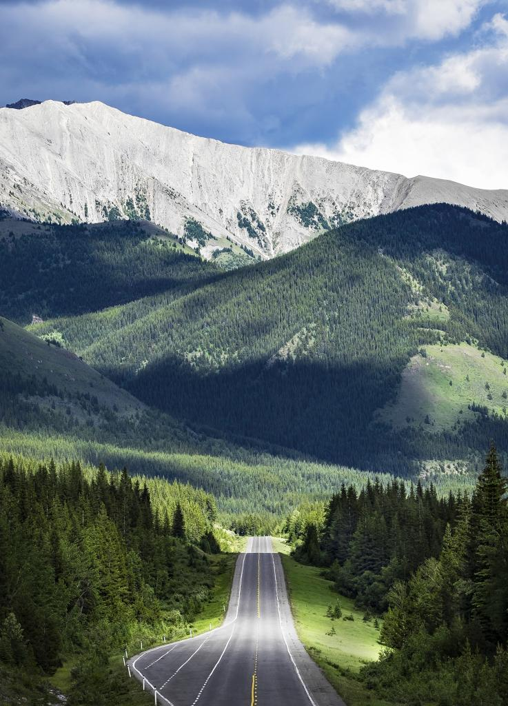 This photograph was taken at the end of a month long journey across Canada. It was cloudy most of the day and we were driving parallel to a storm. Luckily the sun started to break through and the plump clouds and bright sun made a beautiful contrast across the mountainous   landscape.