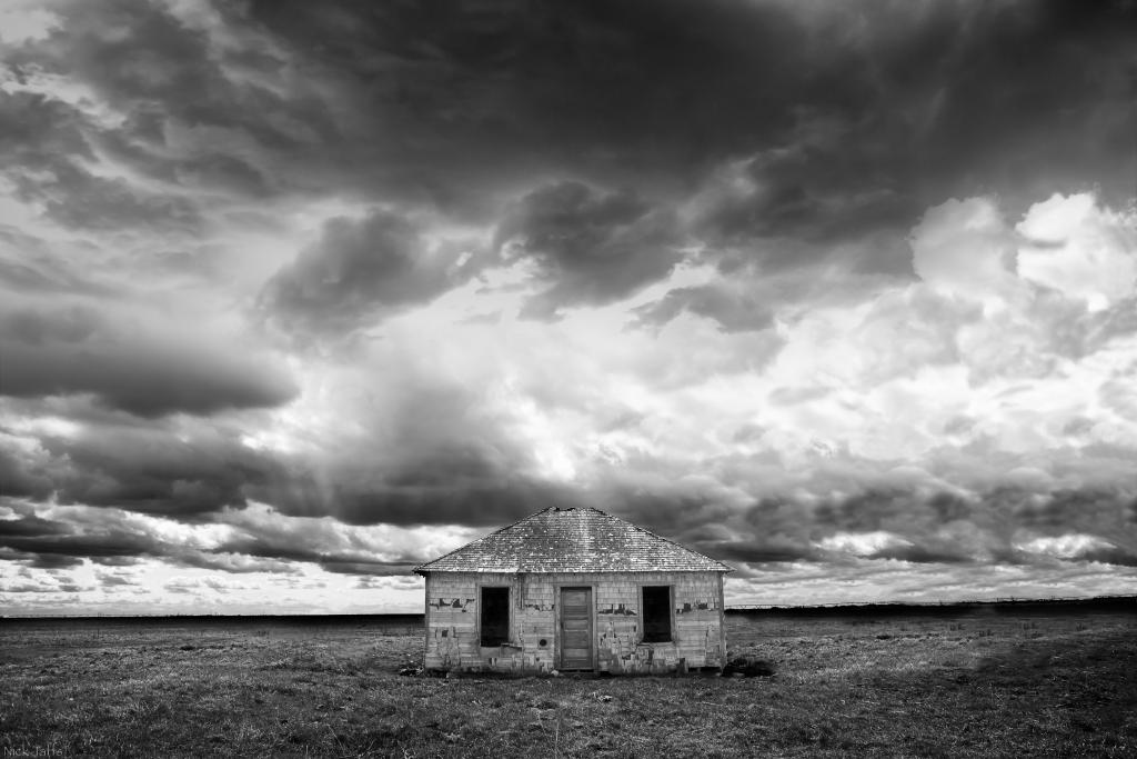 An old abandoned farm house stands alone weathering away over time just outside of Dinosaur Provincial Park, Alberta.