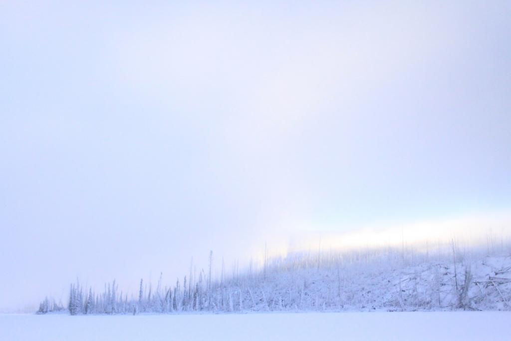 Snow covers every inch of Little Fox Lake in Whitehorse, Yukon, while the sun illuminates a small hill.