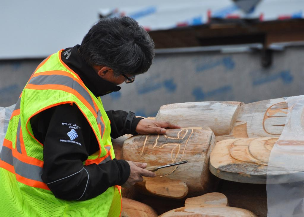Inuit carver and Atanarjuat director, Zacharias Kunuk, carving Reconciliation Pole