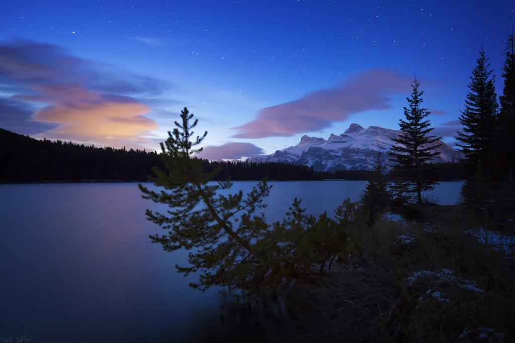 A framed view of Cascade Mountain from Two Jack Lake in Banff Alberta. The clouds glow in the distance from the Banff townsite.