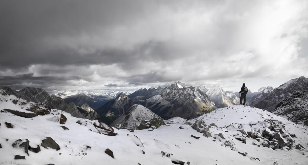 A solo hiker takes a moment to take in the vast beauty of his surroundings before pressing onward in Kananaskis, Alberta Canada.