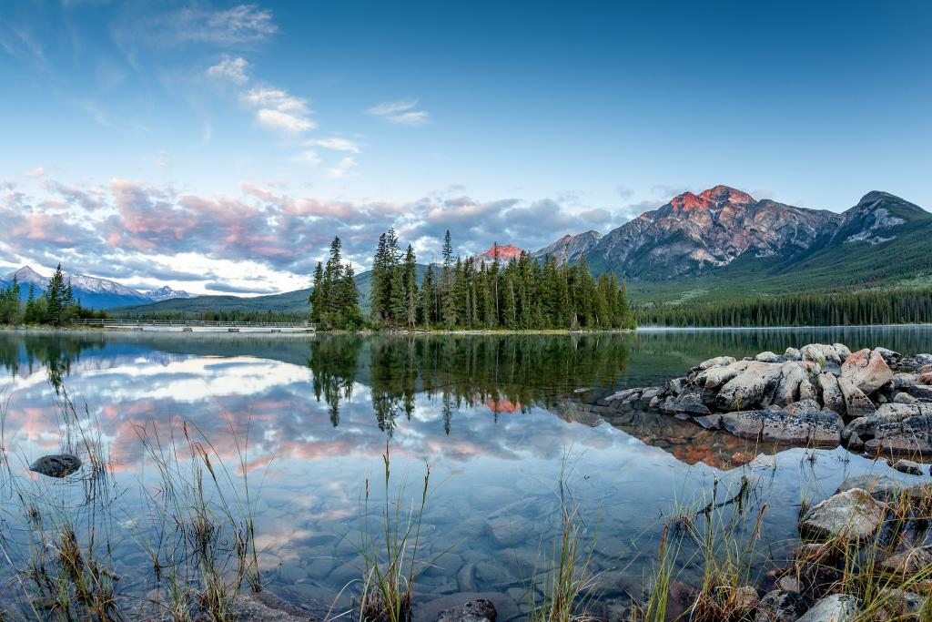While camping at Jasper National Park in Alberta, I decided with a group of friends to catch the sunrise at nearby Pyramid Lake. We were not disappointed. As the sun rose, its rays lit up the top of Pyramid Mountain and the clouds, reflecting off the serene lake and creating this surreal landscape.