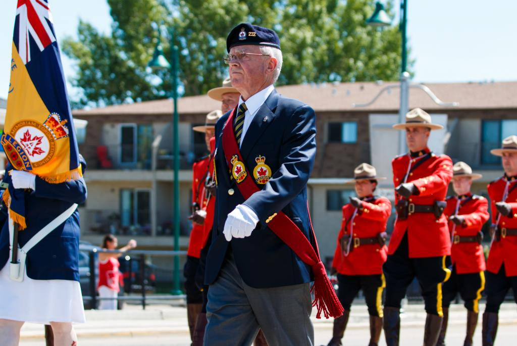 Every Canada Day in Sylvan Lake, Alberta, a flag raising ceremony is held followed by a walk down the main street of the town. People included in this march are members of the Canadian Legion, RCMP, veterans, and followed by everyday citizens. This picture shows a member of the Canadian Legion followed by the RCMP.