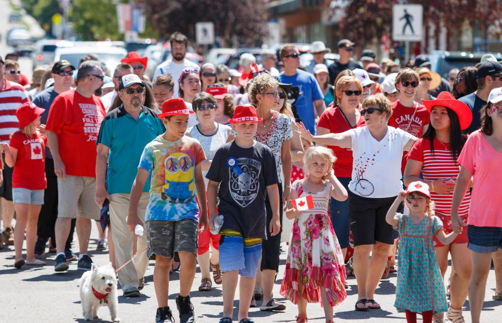 Every Canada Day in Sylvan Lake, Alberta there is a flag raising ceremony followed by a march down main street. This march includes members of the Canadian Legion, RCMP, veterans, and citizens. This photo shows many citizens of Sylvan Lake and Canada marching down the middle of the street.