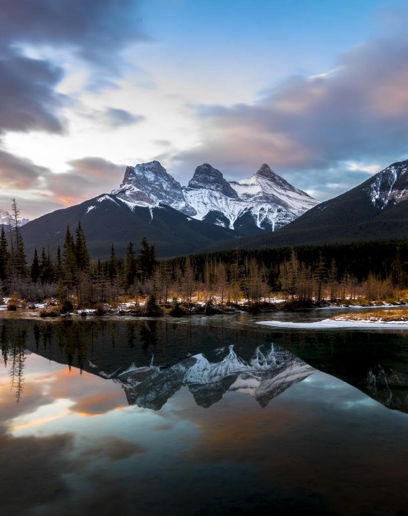 Early morning sunset and calm winds reflect the ever present beauty of the Three Sisters, located near Canmore, Alberta.