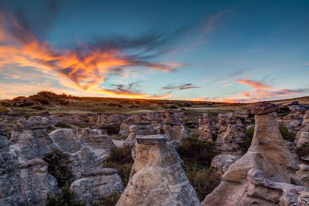 While camping at Writing-on-Stone Provincial Park in  in Alberta, I was mesmerized by the dramatic sunset over the Hoodoo badlands and quickly took out my camera to take this picture. Also known as Áísínai'pi National Historic Site, the area contains the largest concentration of First Nation petroglyphs (rock carvings) and pictographs (rock paintings) on the great plains of North America.