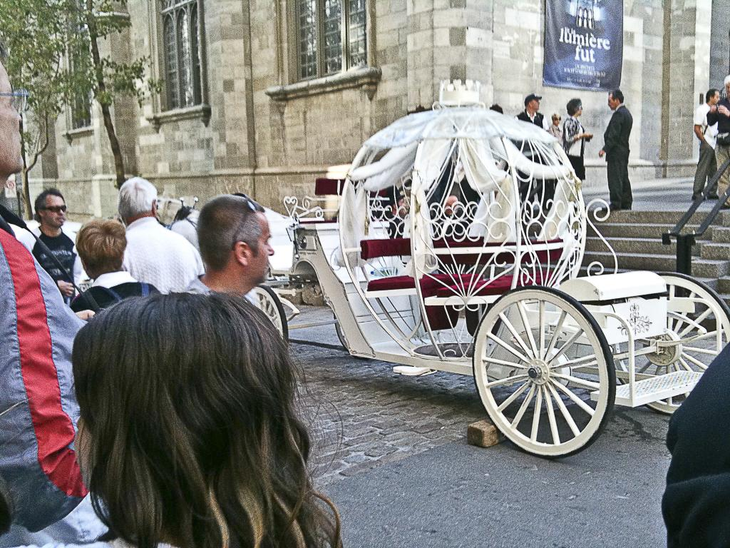 a fairytale carriage awaits outside l'église nôtre dame in old montreal.