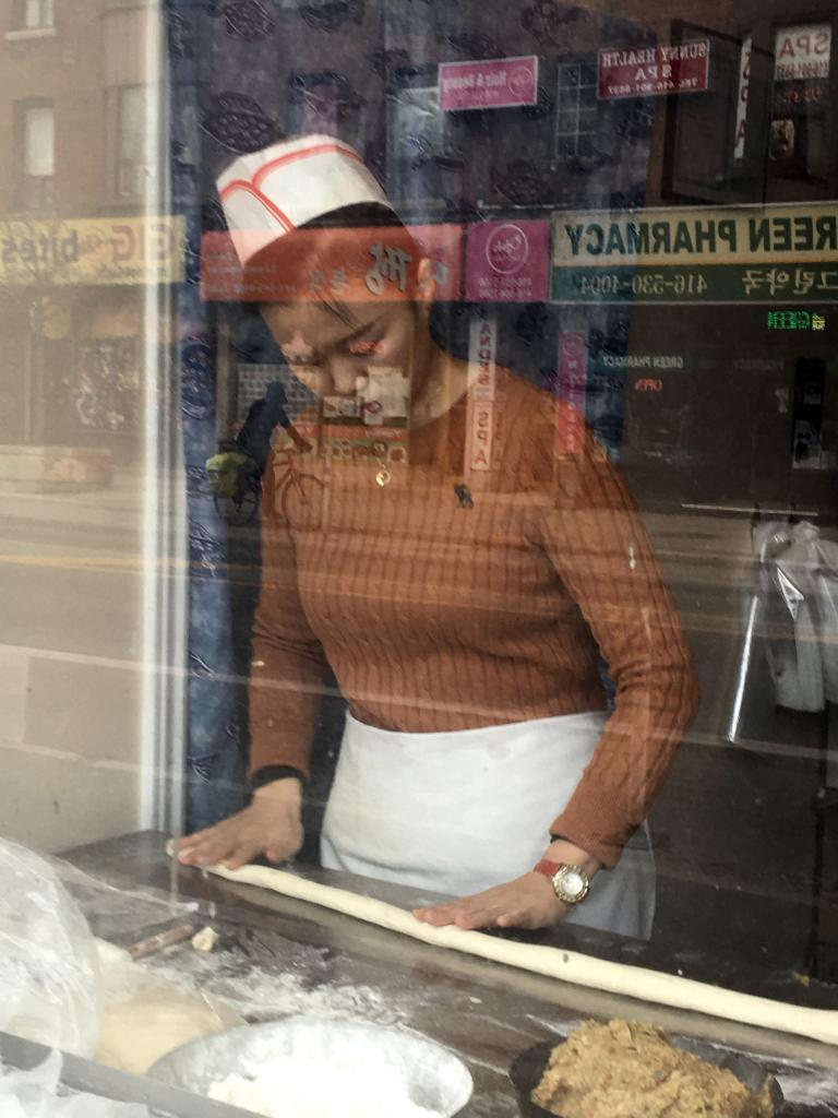 A woman rolling dumplings in Korea town on Bloor Street - Toronto